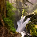 Light putting on a show as it dances in the mist of Sol Duc Falls.- 10 Amazing Day Hikes in Olympic National Park