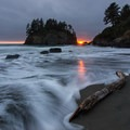 The sun peaks out from a gap in the cloud bank as gentle waves creep across the short beach.- Trinidad State Beach