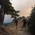 PCT thru-hikers gather as smokey skies from a fire near Mount Adams set the back drop for this water break in Goat Rocks Wilderness, Washington.- America's Incredible Thru-Hikes