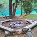 A campsite fire ring at Bowman Lake Campground.- Head of Bowman Lake Campground