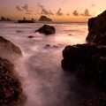 A warm glow from the setting sun illuminates the tiny barnacles clung to the rocky little cove.- Short Beach