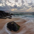 Waves crash on the yellow sand during a cloudy sunset- Ho'okipa (H-Poko) Beach Park + Overlook