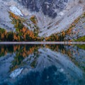 Golden Larches scatter the hillside below Dragontail Peak, reflecting in the still Colchuck Lake- Colchuck Lake Trail
