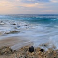 Waves rush across the rocky beach at sunrise.- Keawaula Beach