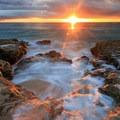 Sunset over rocky coast on Lualualei Beach.- Lualualei Beach Park