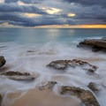 Waves crashing over rocky coast during a cloudy sunset on Lualualei Beach.- Lualualei Beach Park