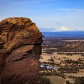 Climbers ascend Monkey Face with Mt Jefferson on the horizon.- Smith Rock, Misery Ridge Hiking Trail