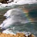 A rainbow forms behind a wave- Pfeiffer Beach
