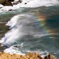 A rainbow forms behind a wave- Pfeiffer Beach