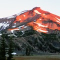 South Sister turns a rose-orange hue as it catches the morning sun over the lakes- Green Lakes