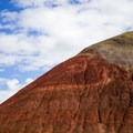 Red Hill is vibrantly colored against a blue and white cloud sky- Painted Hills Unit