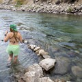 A hot springs visitor enjoys the mixing of hot and cold water at the river's edge- Kirkham Hot Springs