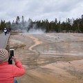 Cheryl taking a photo of a geyser field.- Wolf Tracking in Yellowstone National Park