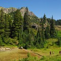 Hikers along Eunice Lake's shore under Tolmie Peak.- Mount Rainier's 7 Best Day Hikes