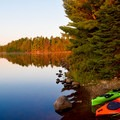 Kayaks moored at a campsite at sunrise.- A Beginner's Guide to Paddling the Boundary Waters Canoe Area Wilderness