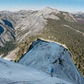 A climber descends the cables in late October with breathtaking views of Clouds Rest, Tenaya Canyon and other Yosemite vistas in all directions.- Climbing Half Dome In The Shoulder Season