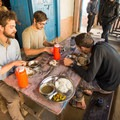 The team tucks in to Nepal's staple dinner: Dal Bhat.- The Realities Behind The Journey