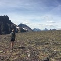 A hiker pauses during a ridgeline traverse in Glacier National Park. Photo by Emily Downing.- Woman In The Wild: Emily Downing