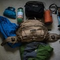 Packing for the day: Kit cube at the top (DSLR with 50mm and 35mm lens), two jackets, first-aid kit, Nalgene, bothy bag, trekking poles, and some room left over.- Gear Review: Mountainsmith Tanack 10L Lumbar Pack