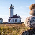 A cairn sits to the southeast of the Point Wilson Lighthouse, which is visible on paddles outside of Port Townsend.- 50 of Washington's Best Sea Kayaking Adventures